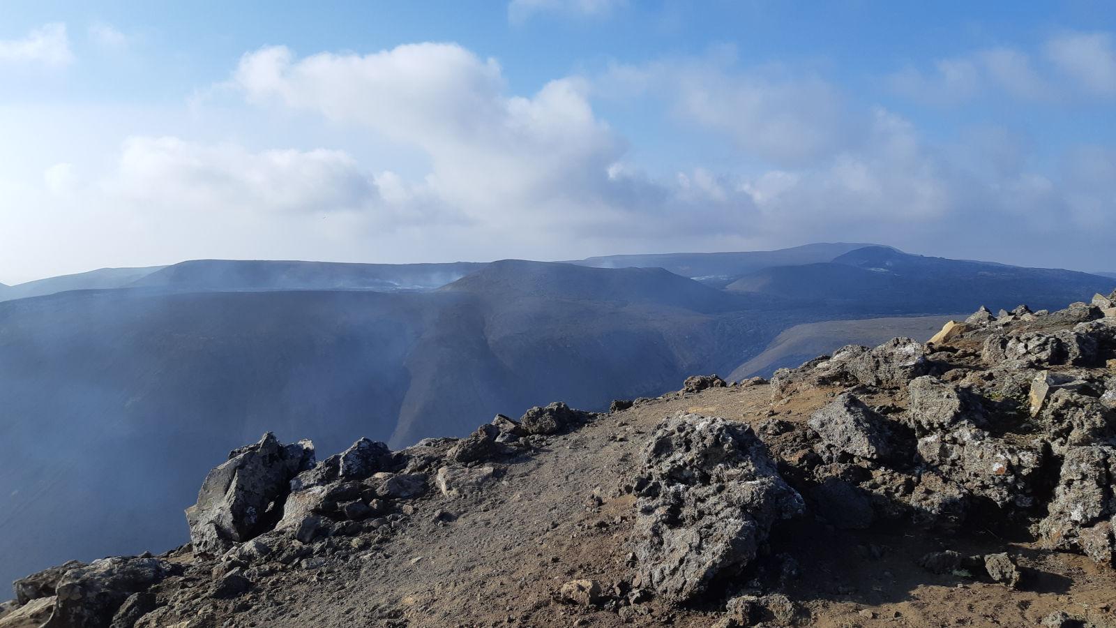 Im Hintergrund dampfend, der Krater des Fagradalsfjall.